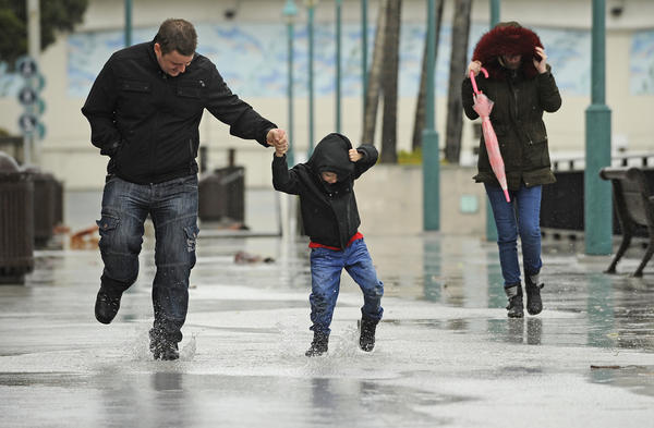 Scott Hesford-Hensler, left, plays in the rain with his son Jayden, 5, and wife, Danielle, at King Harbor in Redondo Beach. (Christina House / For The Los Angeles Times)