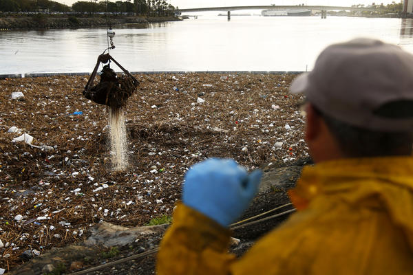 Bitelio Ramirez looks out Thursday over trash that has piled up near the mouth of the Los Angeles River after two days of heavy rain. A worker on the scene said two cranes were being used to lift out about 300 tons of trash. (Rick Loomis / Los Angeles Times)