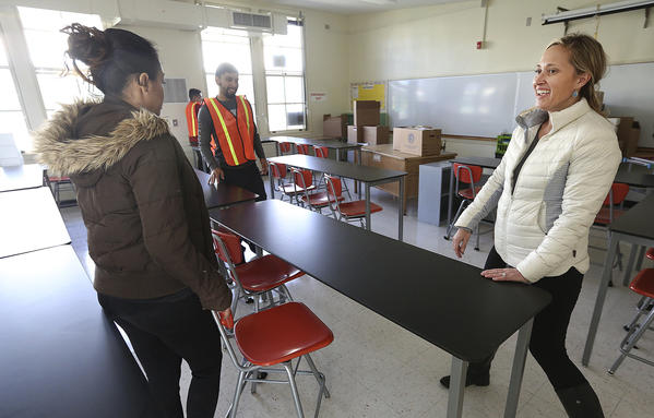 Porter Ranch Community School science teacher Rosie Van Zyl moves tables with the help of other LAUSD employees in her new classroom at Northridge Middle School. (Mel Melcon / Los Angeles Times)