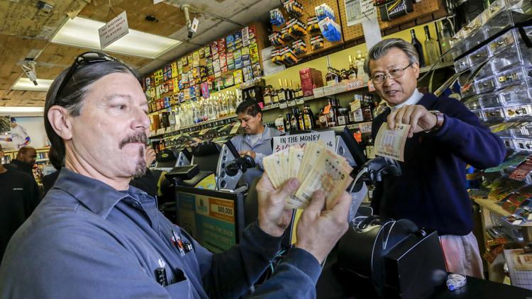 Mark Nelson, left, shows off $460 worth of Powerball lottery tickets he bought at Bluebird Liquor, a shop with a reputation for lottery luck, in Hawthorne. At right is the owner of the liquor store, James Kim.