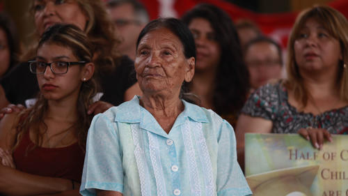 Rosalia Garcia de Flores, center, listens at a news conference in Pacoima launching a campaign to register Latino voters in mixed-status families. (Katie Falkenberg / Los Angeles Times)