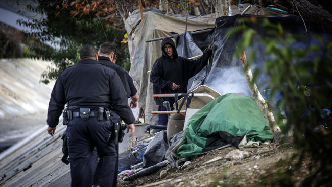 LAPD officers approach a homeless man camped along the Arroyo Seco on Jan. 13. (Los Angeles Times)
