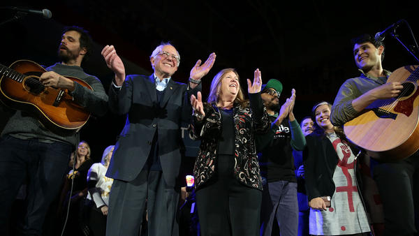 Bernie Sanders and his wife, Jane O'Meara Sanders, join Vampire Weekend on stage at a campaign event in Iowa City. (Alex Wong / Getty Images)