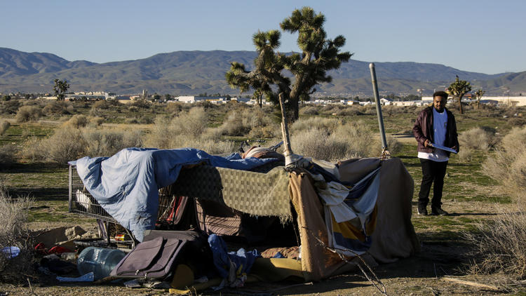 Derrick Chambers checks out a homeless  encampment in the Lancaster desert during the annual homeless census in January. (Los Angeles Times)