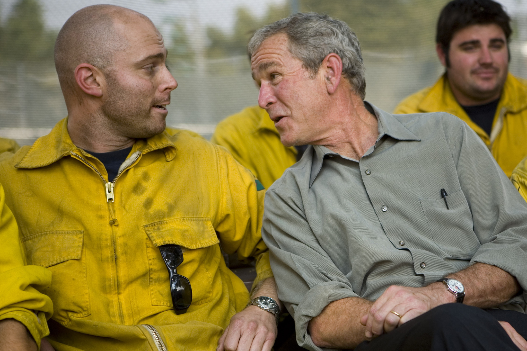 President George W. Bush jokes with a fire crew member after touring the Rancho Bernardo area in San Diego in October 2007.