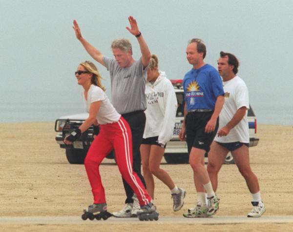 As President Clinton finishes his morning jog with a stretch in June 1996, Emily Kroll of Santa Monica skates by.
