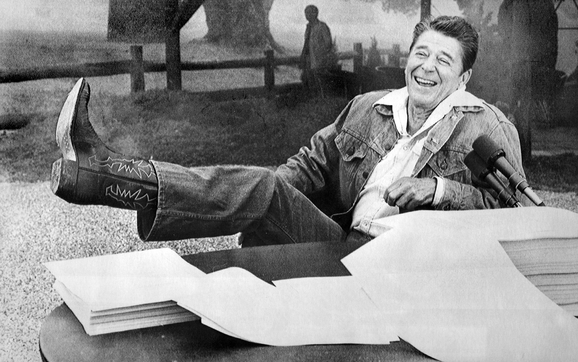 While in Santa Barbara in the summer of 1981, President Reagan shows his boot to reporters who asked if he had any problems with the bubonic plague threat in the area. In front of him lies the economic tax relief bill and budget that he signed while on vacation.