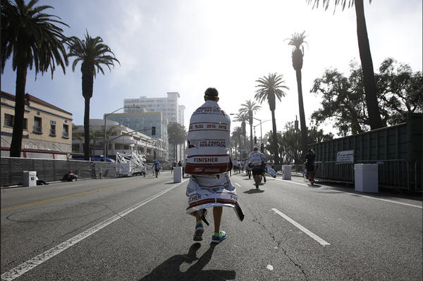 A runner walks along Ocean Boulevard in Santa Monica after completing the L.A. Marathon. (Robert Gauthier / Los Angeles Times)