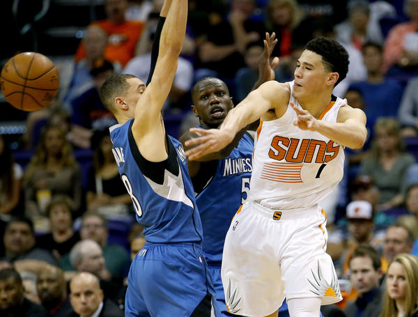 Suns rookie Devin Booker, right, passes around the Timberwolves' Zach LaVine during the first half of a game on March 14.