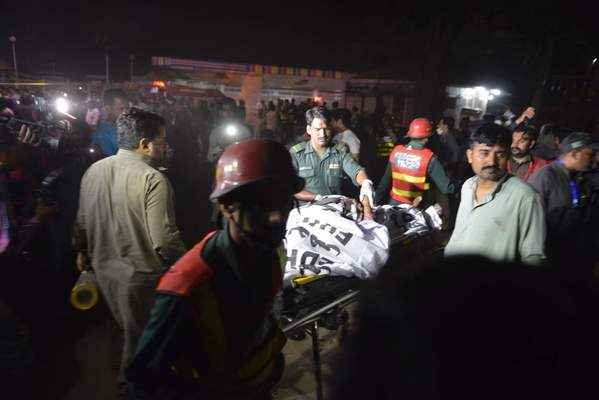 Pakistani rescuers use a stretcher to shift a body from a bomb blast site in Lahore.