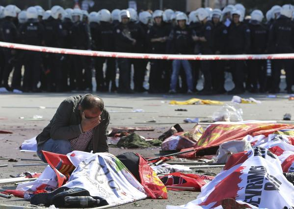 A man cries over the body of a victim at the site of an explosion targeting a peace rally in Ankara, Turkey.