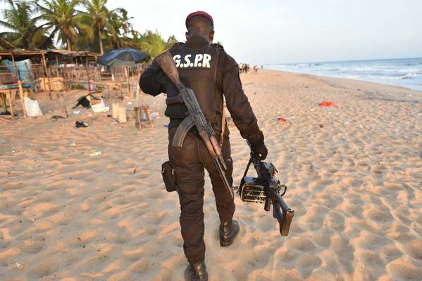 An Ivory Coast soldier carries a machine gun as he walks on the beach resort of Grand Bassam after gunmen went on a shooting rampage.