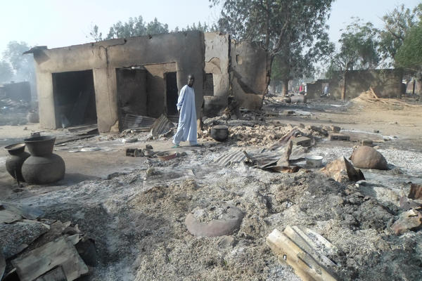 A man walks past burned-out houses after an attack by Boko Haram in Dalori, Nigeria.