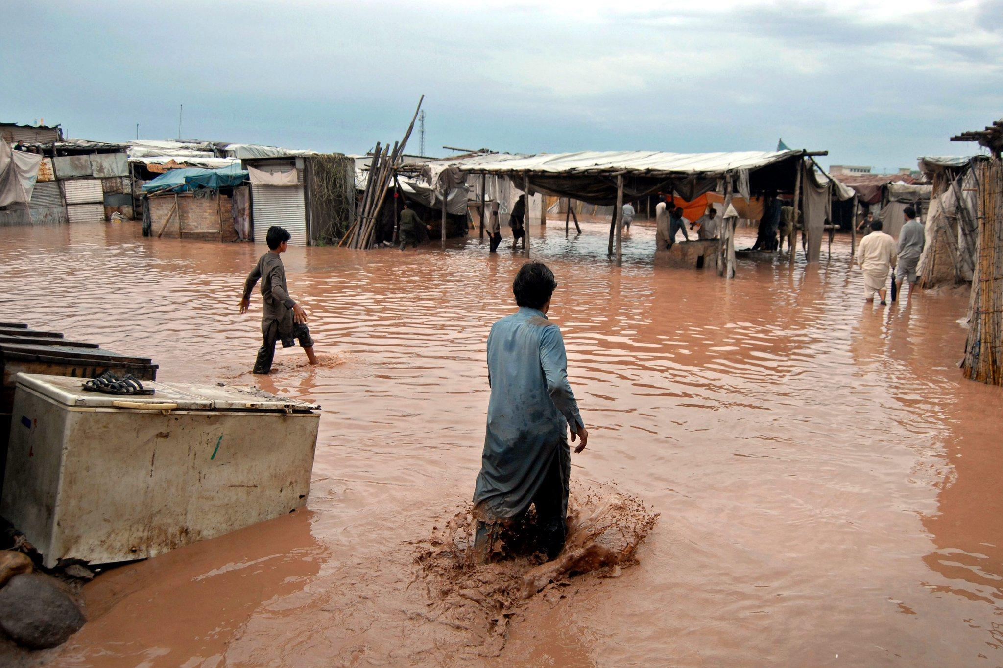 People gather around what is left of their shops after the floods swept through on the outskirts of Peshawar.