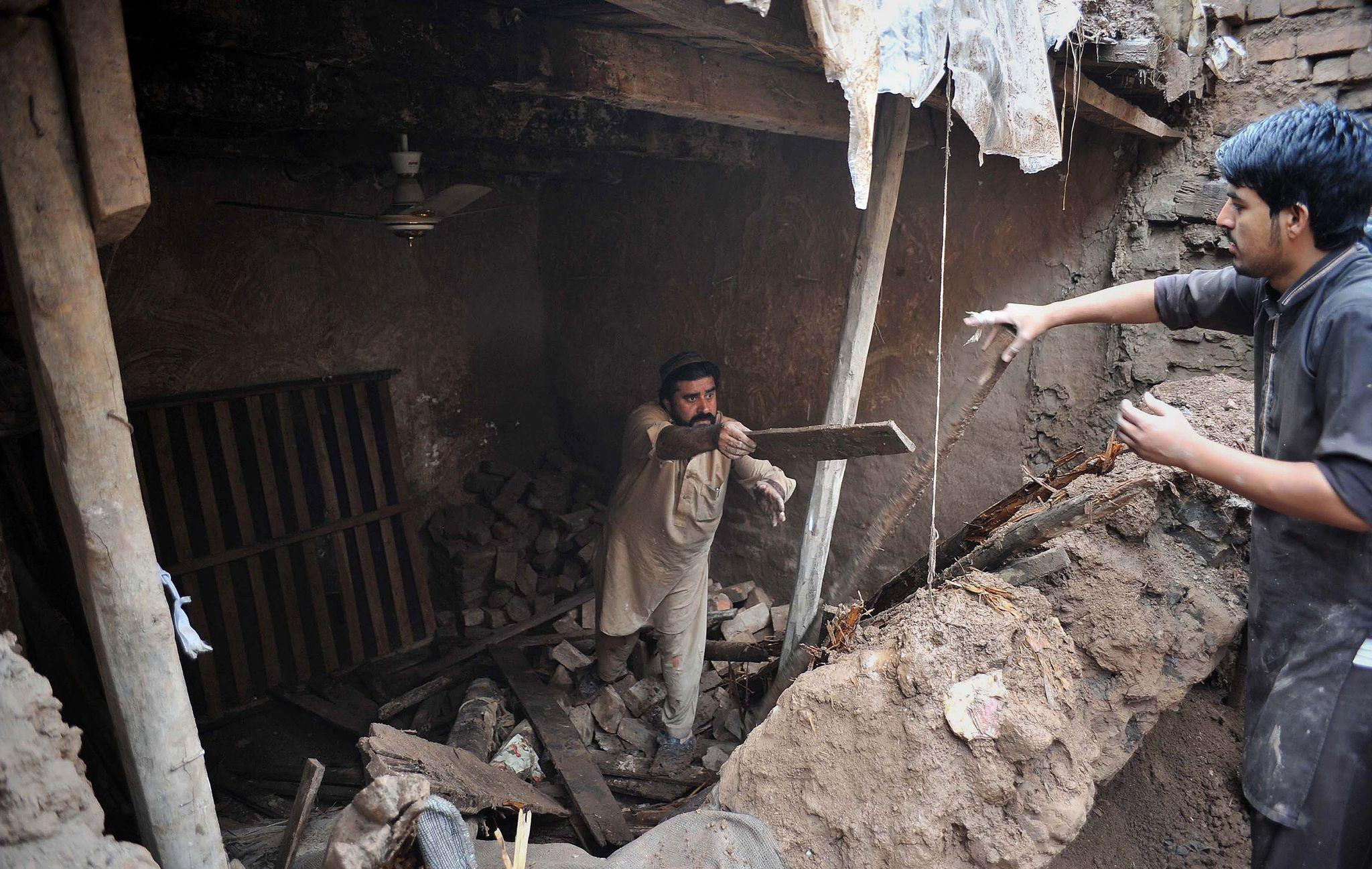 People remove debris from a damaged house after heavy rains devastated the outskirts of Peshawar on April 3, 2016.