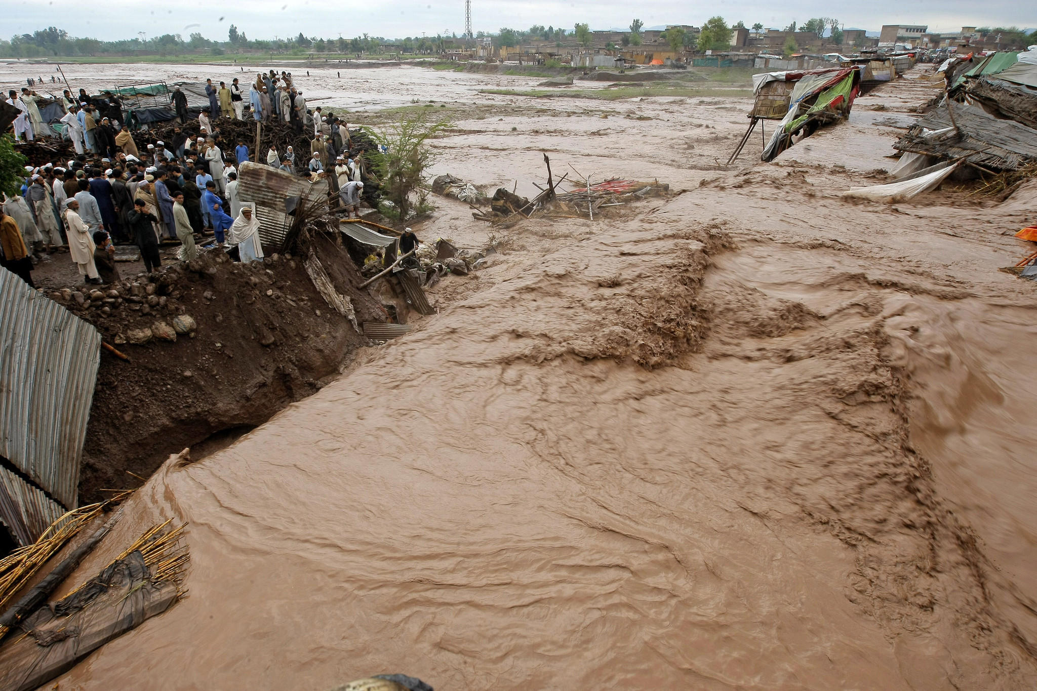 Villagers watch water rush in during a flash flood.