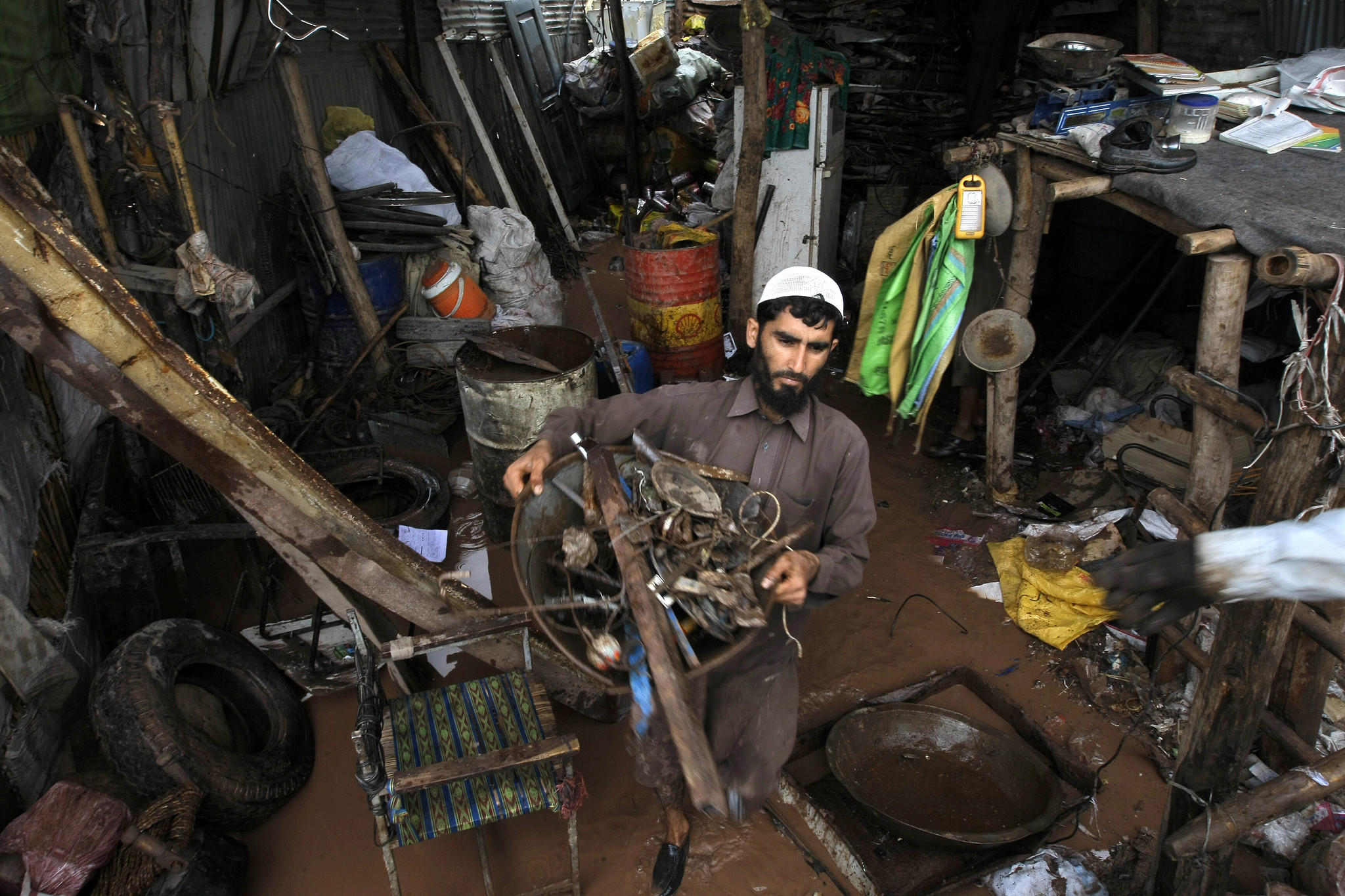 A man salvages his belongings from his flooded house on the outskirts of Peshawar.