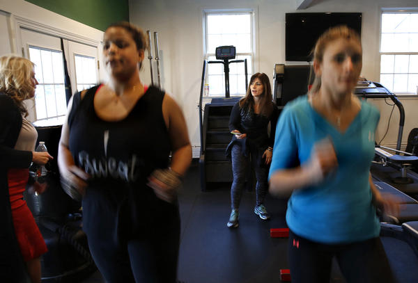 Clients of personal trainer Peggy Hayes, in back, work out in the training gym she built in her northern Virginia home.