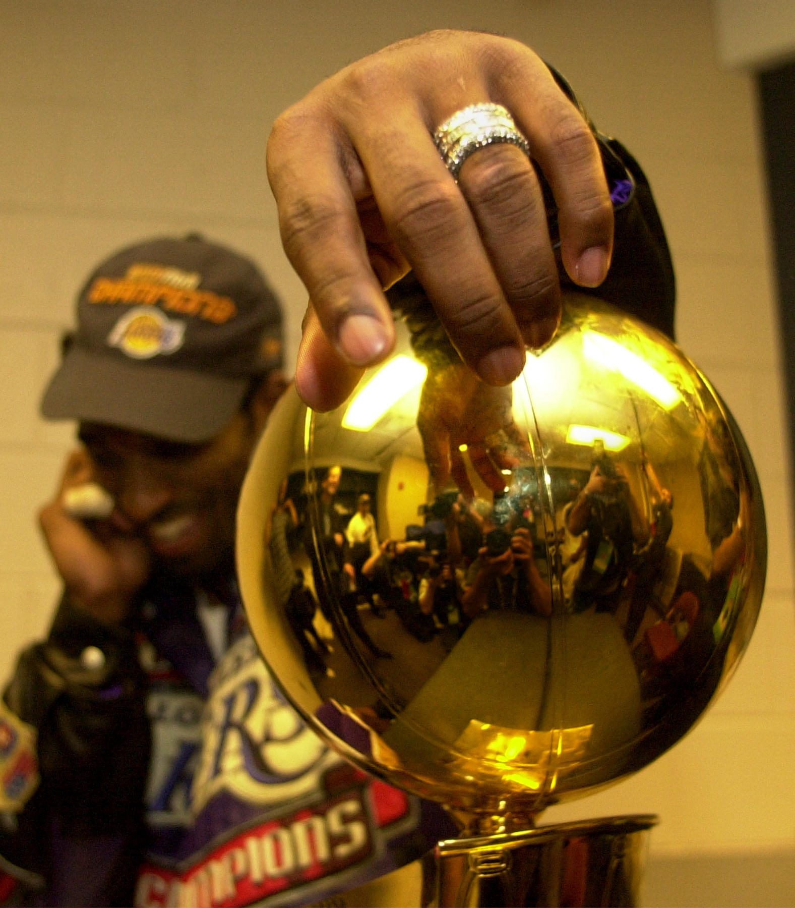 Kobe attempts a reverse layup along the baseline. (Robert Gauthier / Los Angeles Times). Kobe poses with the Championship trophy.
