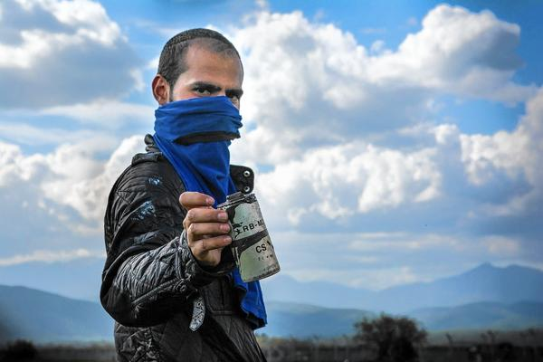 A migrant brandishes a tear-gas canister on April 10 at the Idomeni refugee camp, on the Greece-Macedonia border.