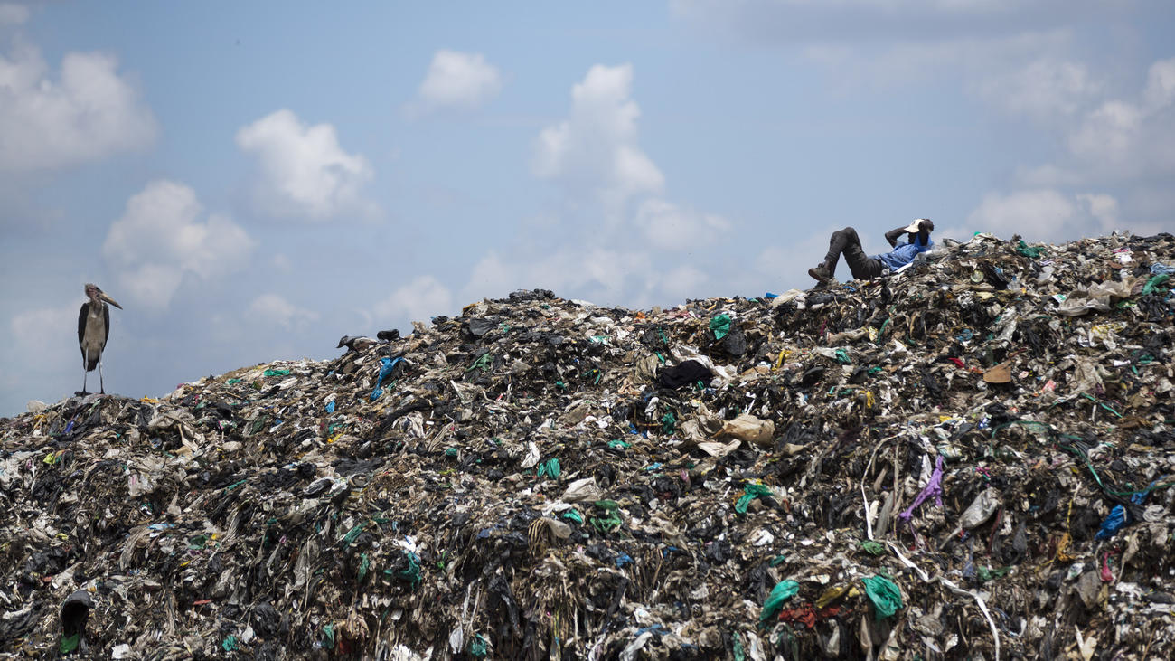 A man who scavenges for a living takes a rest next to a Marabou stork on top of a mountain of garbage at the dump in the Dandora slum of Nairobi, Kenya.
