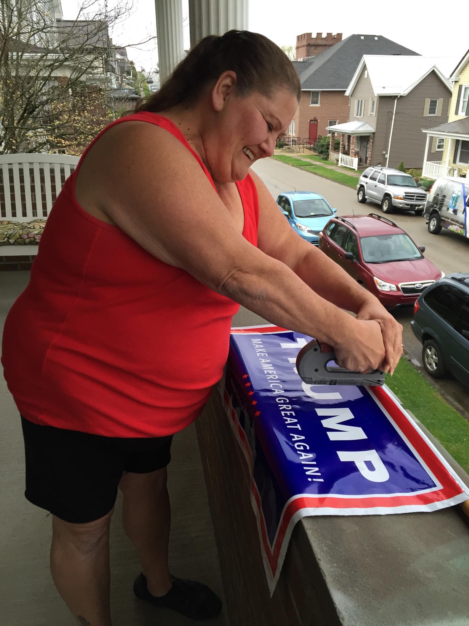Laurie McGinnis on the porch of her home working on a Trump poster.
