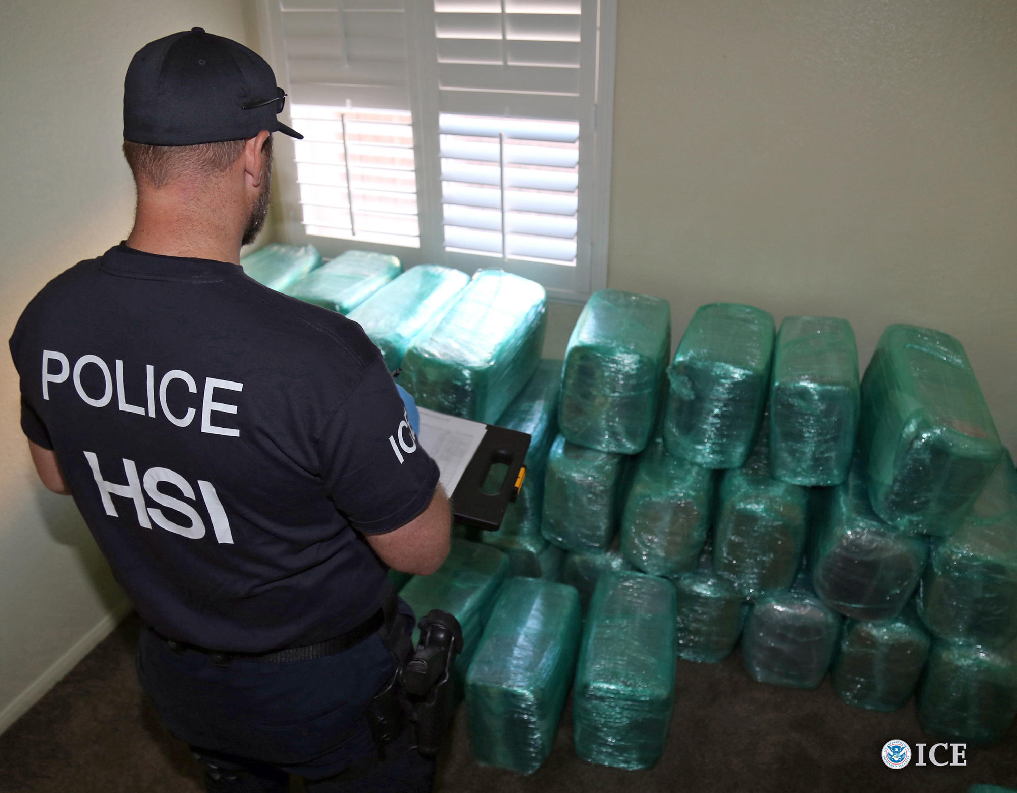A Homeland Security Investigations officer views bags of marijuana stored in a room of a newly built home in Calexico, the terminus of a cross-border tunnel that runs the length of four football fields to a restaurant in Mexicali, Mexico.