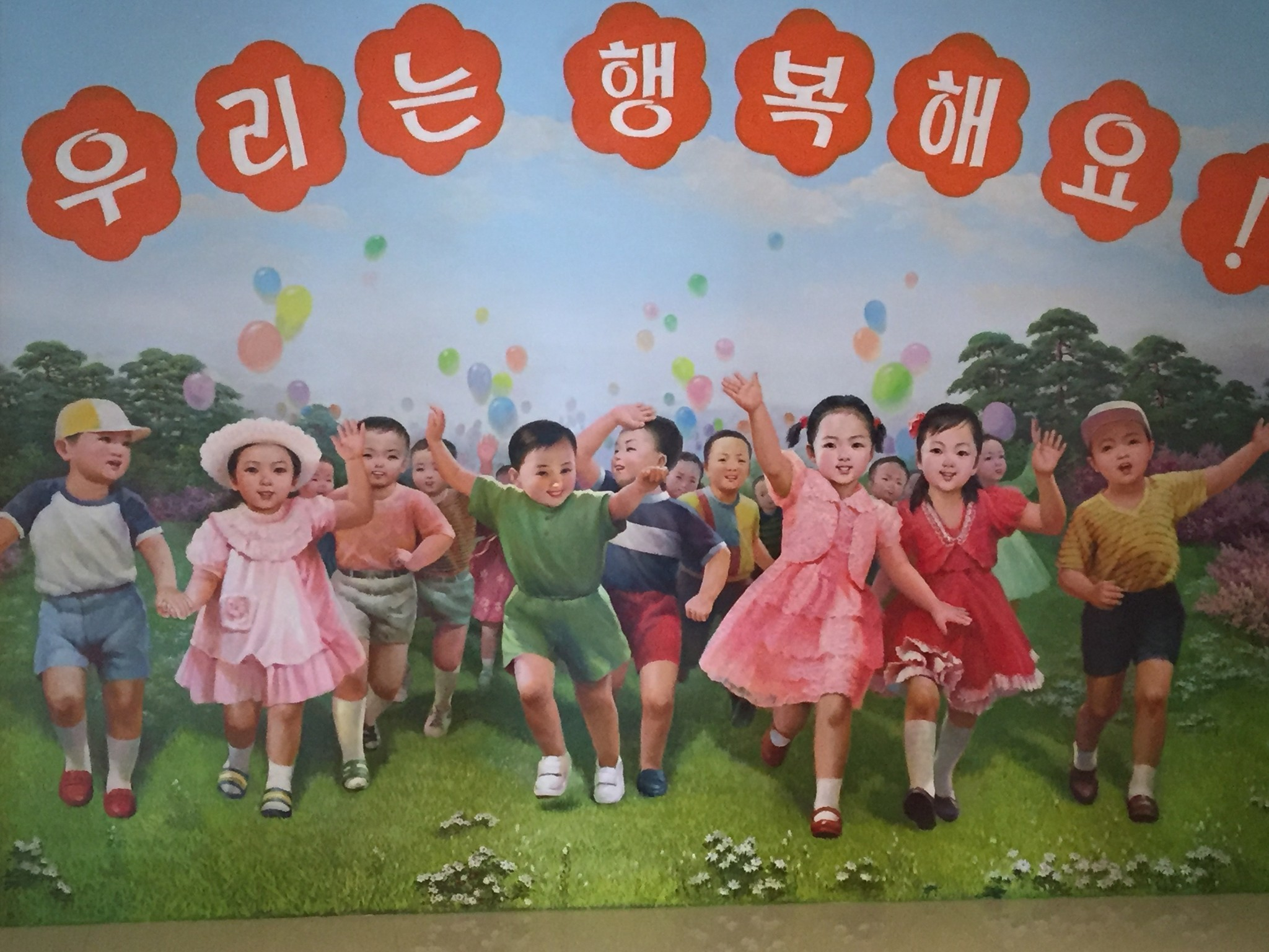 "A mural in the entry hall to the Changchon nursery school says ""we are happy."""