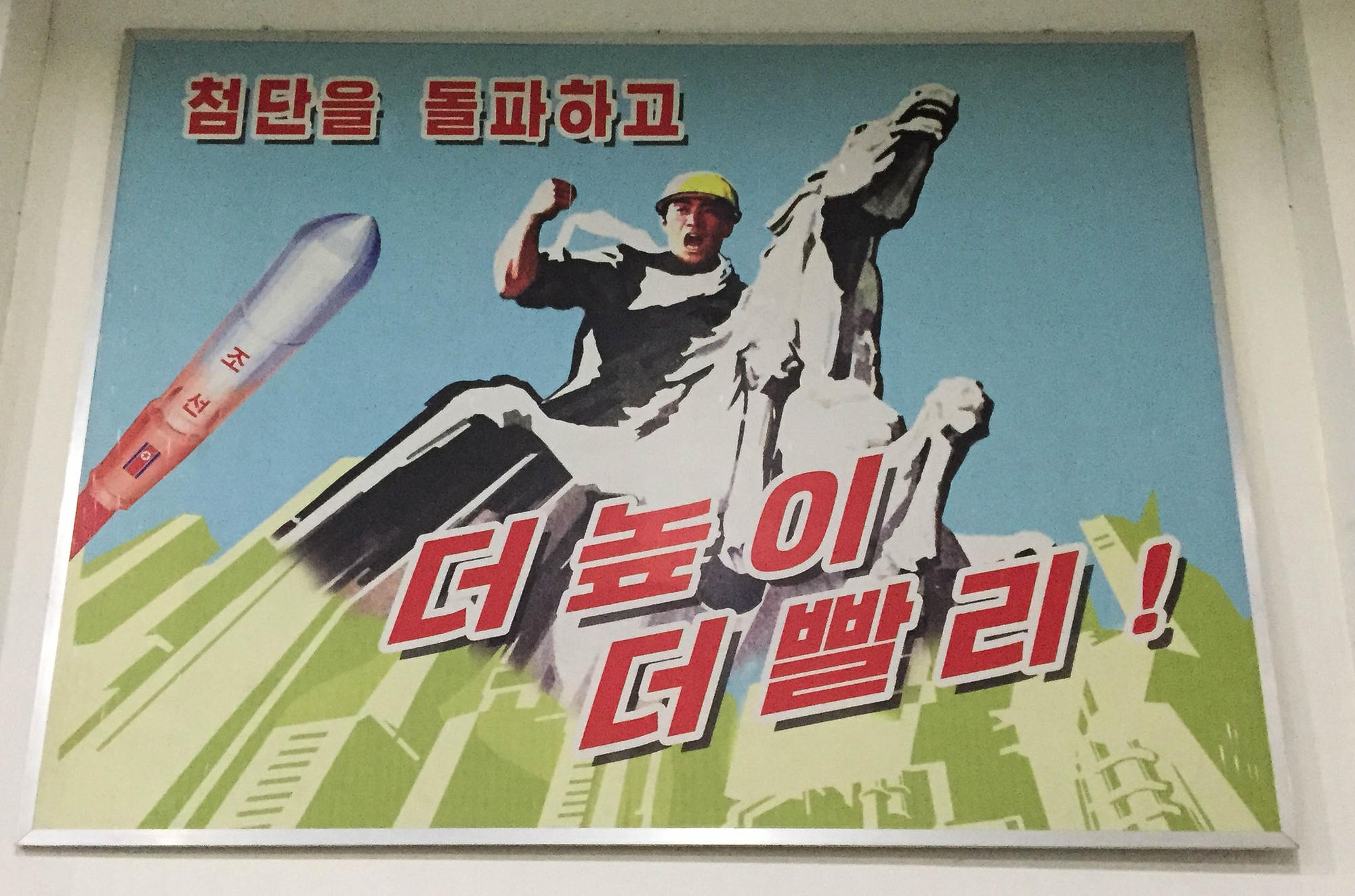 "A piece of propaganda art inside the factory. The plant had numerous large posters exhorting workers to follow the party and work hard for the country. ""Go Higher, Go Faster!"" it says."