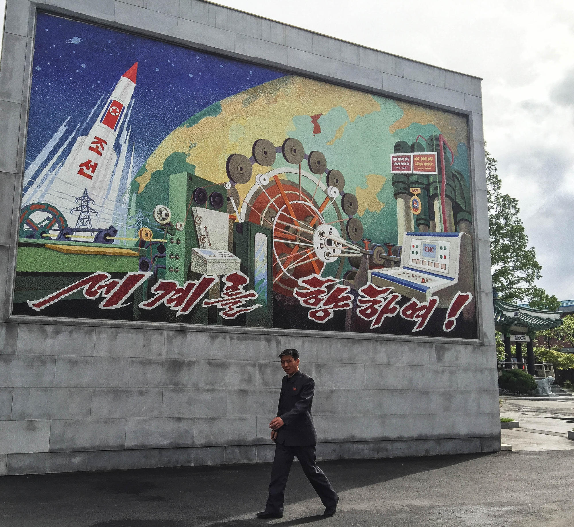 "A mosaic outside the factory showcases North Korea's rocket technology and industrial prowess. It says ""Towards the world!"""