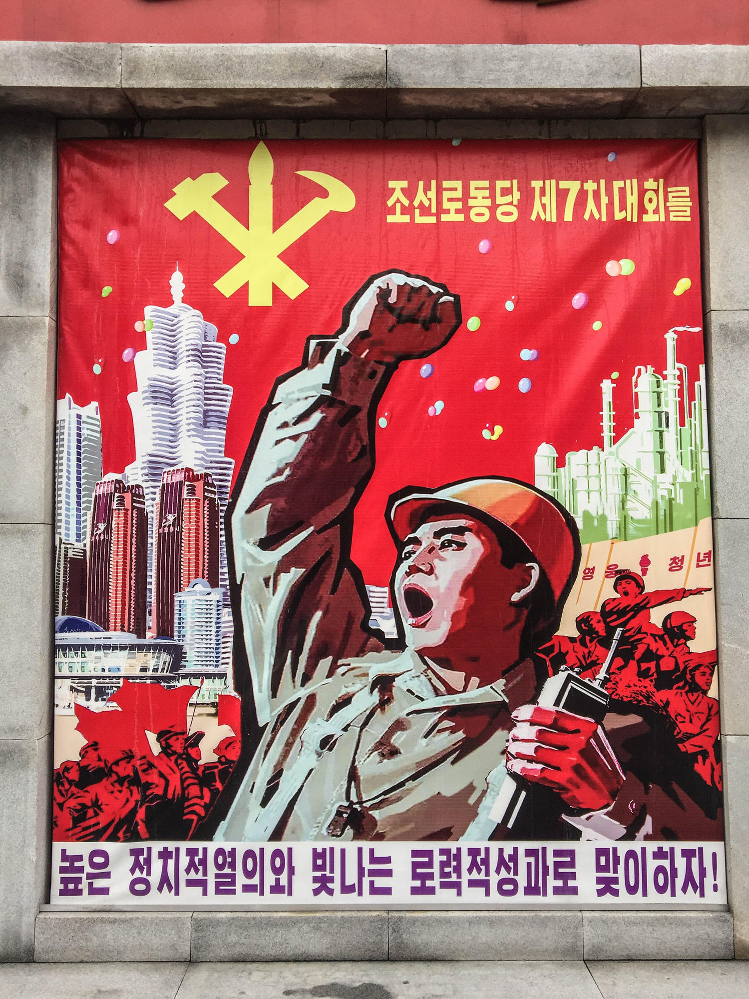 "A piece of propaganda art outside the factory. The poster exhorts workers to work hard ahead of the party congress. Depicted in the background are skyscrapers from the new ""Future Science Street"" in Pyongyang, a residential district for scientists and professors that was built at the behest of Kim Jong Un. It reads:"