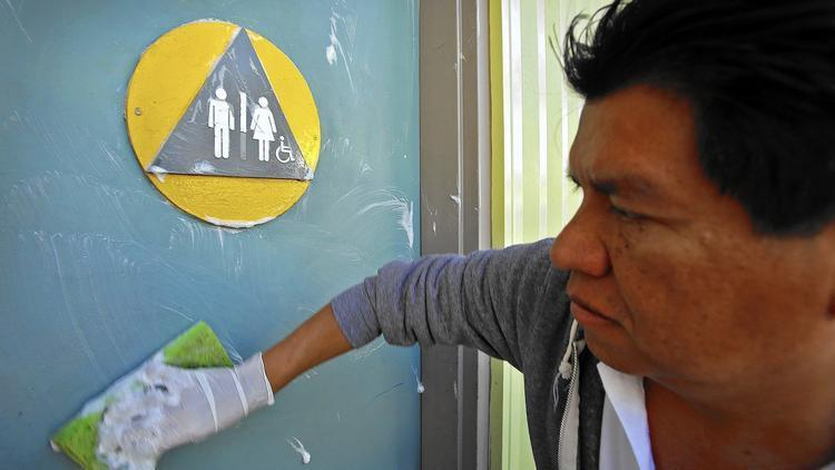 Edgar Lopez, a maintenance worker with the city of West Hollywood, cleans the front door of a restroom at Plummer Park. (Al Seib / Los Angeles Times)