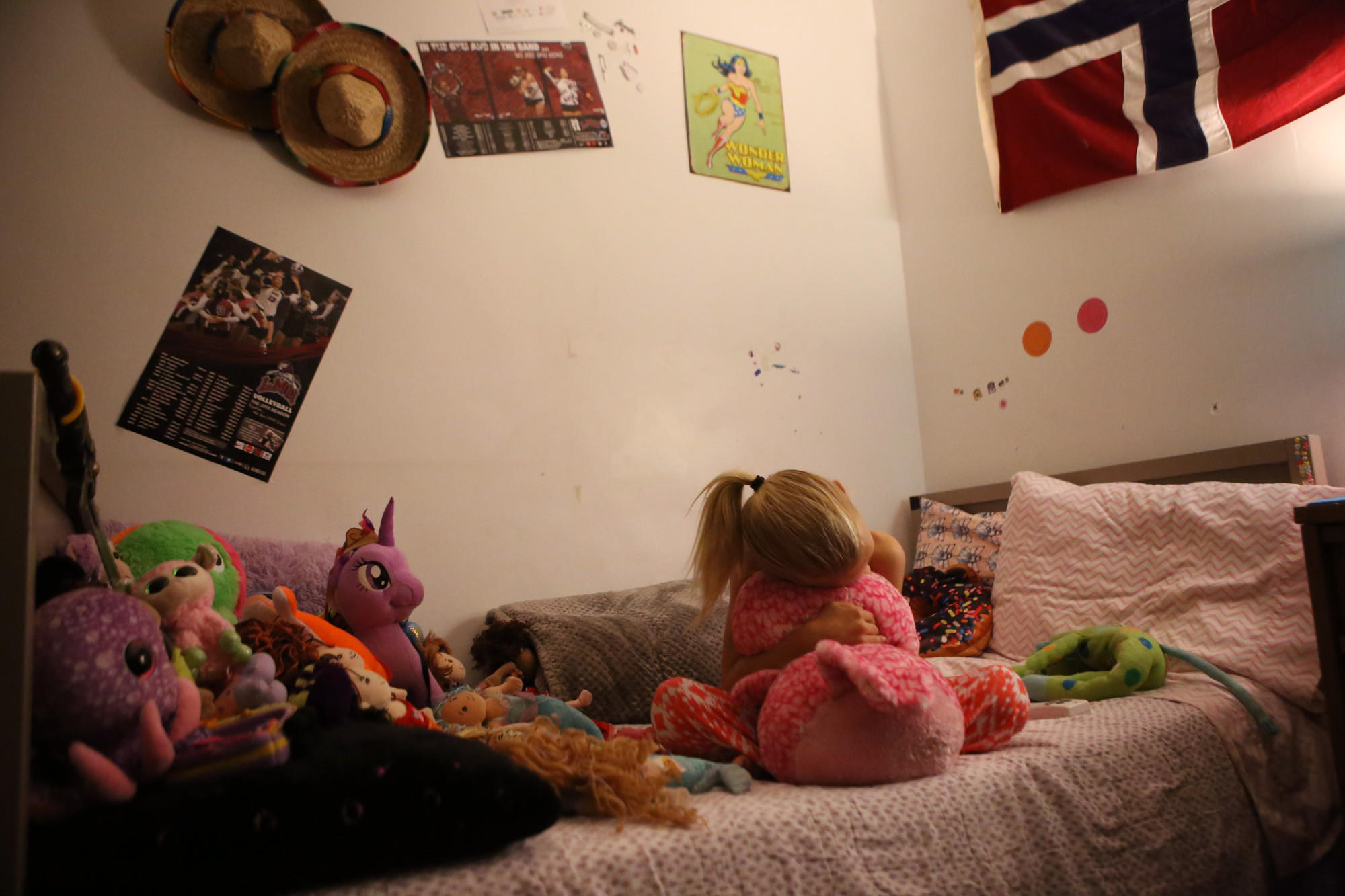 T hugs a stuffed owl on her bed, below a poster of some of her favorite volleyball players.