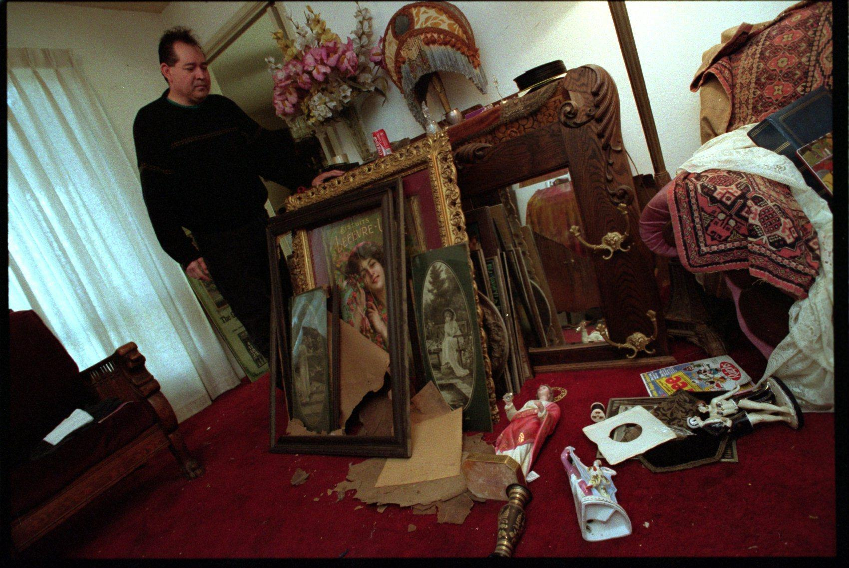 Rick Olguin of Lake View Terrace stands next to rare Victorian paintings from his collection after the 1994 Northridge earthquake. About 50 were damaged in the quake.
