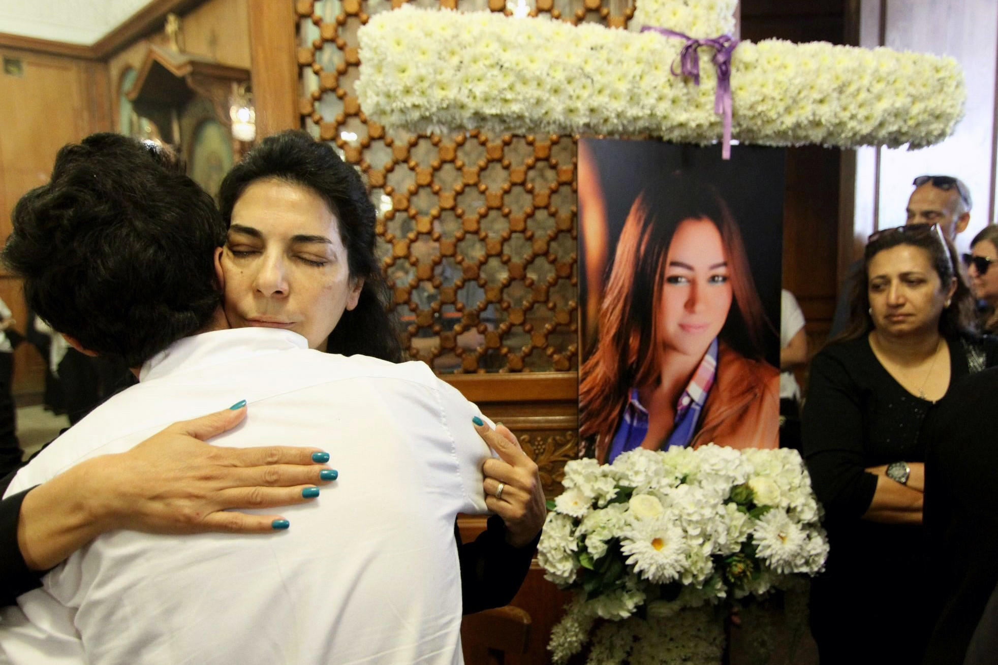 Relatives and friends of EgyptAir flight attendant hostess Yara Hani (portrait), who was on Flight MS804 from Paris to Cairo when it plunged into the Mediterranean, mourn during a ceremony at a Cairo church.