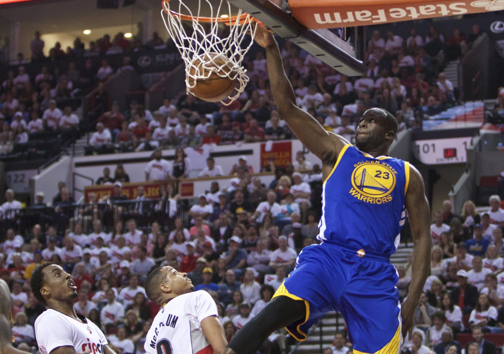 Golden State Warriors forward Draymond Green (23) dunks over Portland Trail Blazers forward Al-Farouq Aminu, left, and C.J. McCollum, on May 9, 2016, in Portland, Ore.