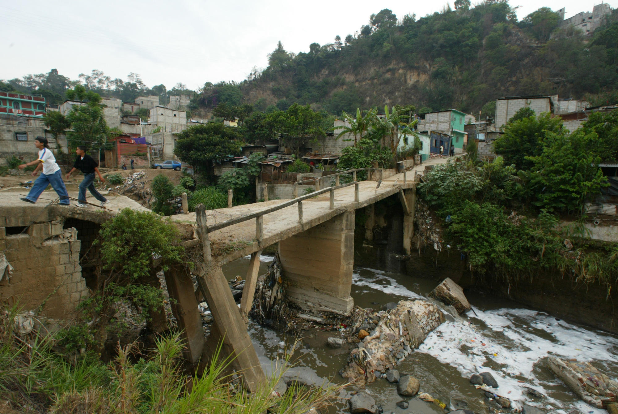 Slum dwellers cross a broken bridge spanning the muddy Rio Las Vacas in Guatemala City where Jose Antonio Guiterrez once lived with his alcoholic father, tubercular mother and two sisters.