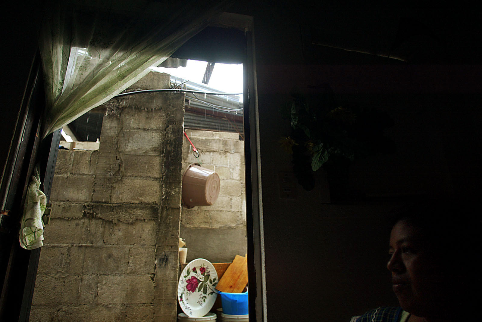 Engracia Cirin sits inside a Guatemala City slum dwelling where she lives with her husband Antonio Paz.