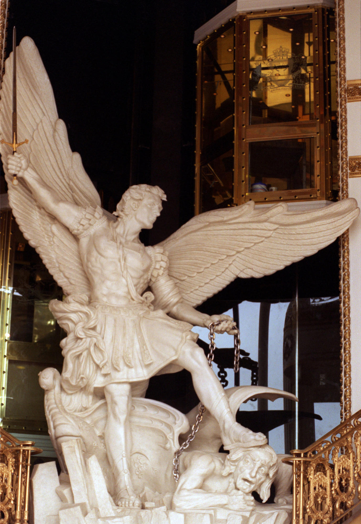 TBN headquarter's entrance features an elaborate 15–foot statue depicting satan being thrown into hell by an angel, behind is a gold and glass elevator.