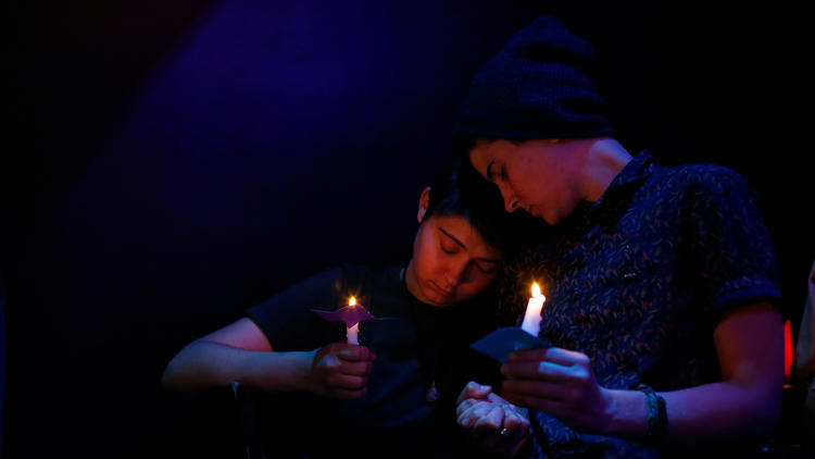Sisters Sarah Bryant, left, and Katy Bryant, both from Irvine, listen as the names of the Orlando shooting victims are read during a vigil at the Velvet Lounge, a gay bar and club in Santa Ana. (Katie Falkenberg / Los Angeles Times)