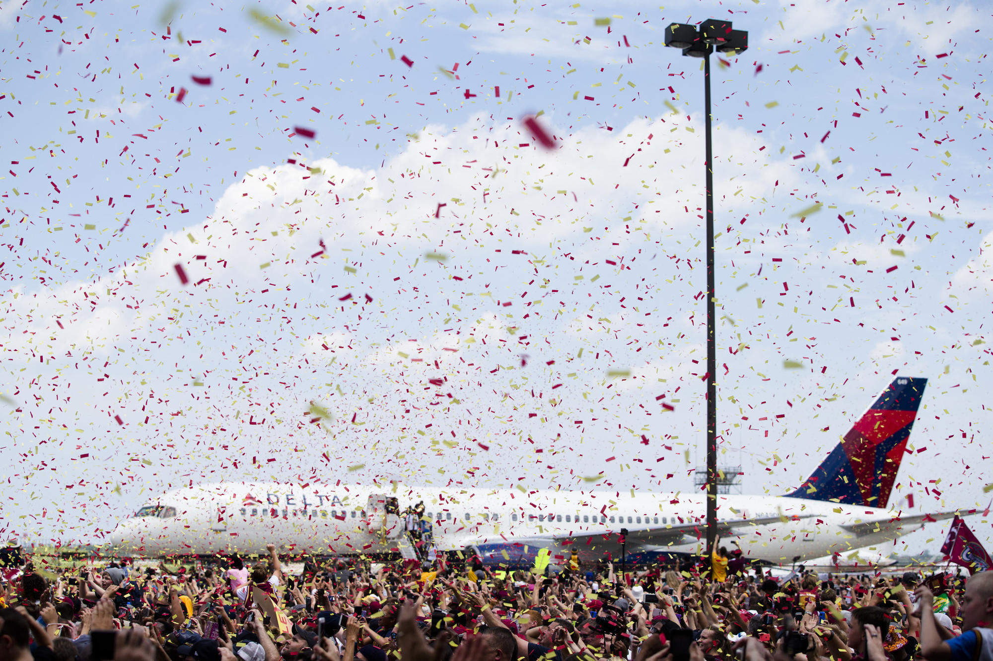 Confetti is sprayed over the crowd as the Cleveland Cavaliers arrive at the airport.