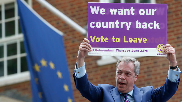 British politician and leader of the UKIP party Nigel Farage holds up a placard in support of Brexit. (Alastair Grant / Associated Press)