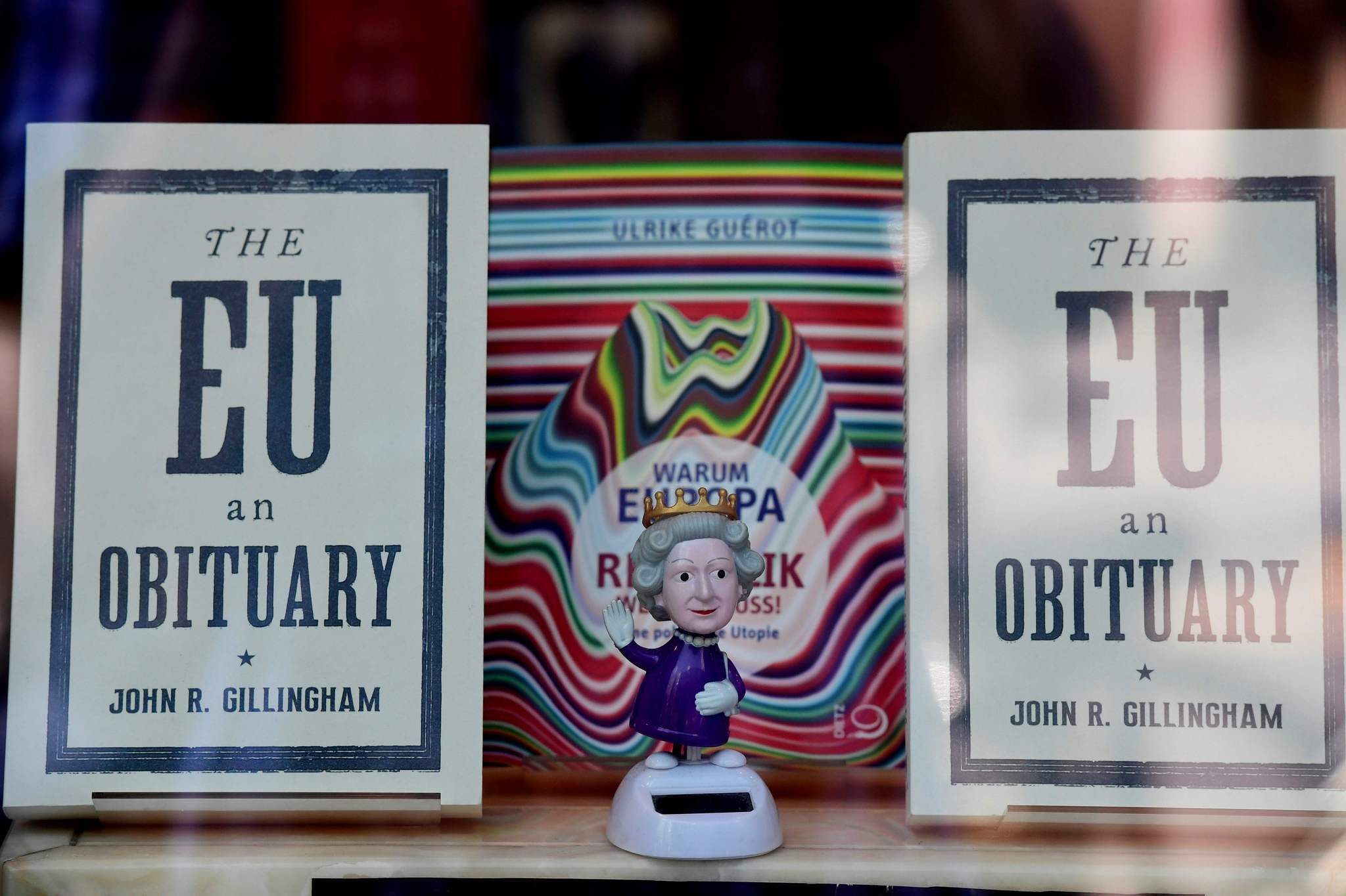 "A figurine depicting Queen Elizabeth II is on display with copies of ""The EU: An Obituary"" by John R. Gillingham in a bookshop window in Berlin. (John MacDougall / AFP/Getty Images)"