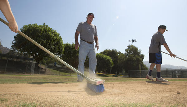 Ted Haller supervises the raking of a mound at the Glendora Little League fields.