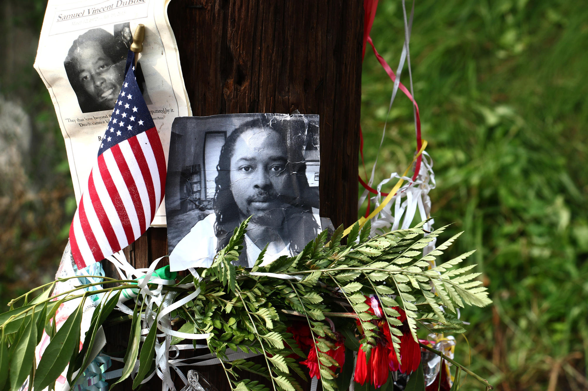 In this July 29, 2015, file photo, photos of Samuel DuBose hang on a pole at a memorial near where he was shot and killed by a University of Cincinnati police officer.