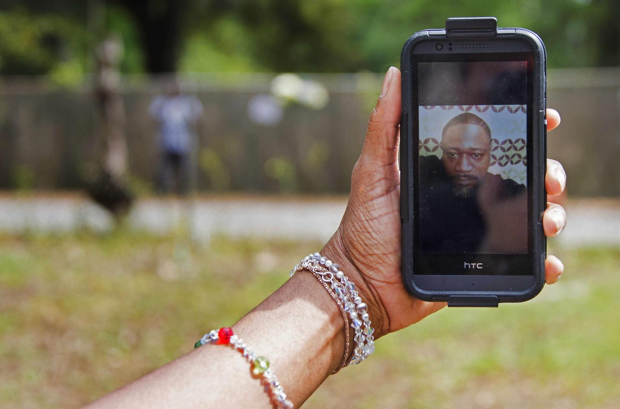 Barbara Scott, cousin of Walter Scott, holds up a picture of Scott on her cellphone in North Charleston, S.C., on April 8, 2015.