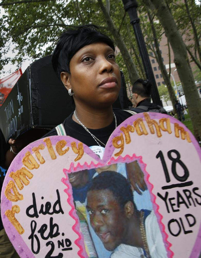 Constance Malcolm, right, holds a photo of her son, Ramarley Graham, who was shot and killed by police.