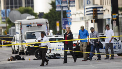 Investigators search the crime scene outside El Centro College in Dallas where a sniper unleashed a barrage of bullets, killing five police officers and wounding seven others. (Marcus Yam / Los Angeles Times)