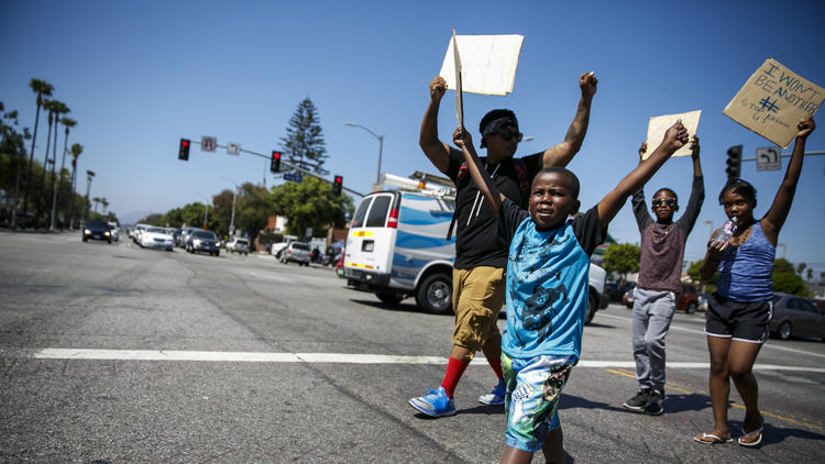 Mac Bevans, left, and Karone Tolliver, 5, march with protesters in Los Angeles on Thursday after the recent deaths of Alton Sterling and Philando Castile at the hands of the police in other states. (Marcus Yam / Los Angeles Times)