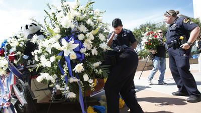 A Dallas police officer wipes away a tear as other officers adjust flowers on a police cruiser. (Barbara Davidson / Los Angeles Times)